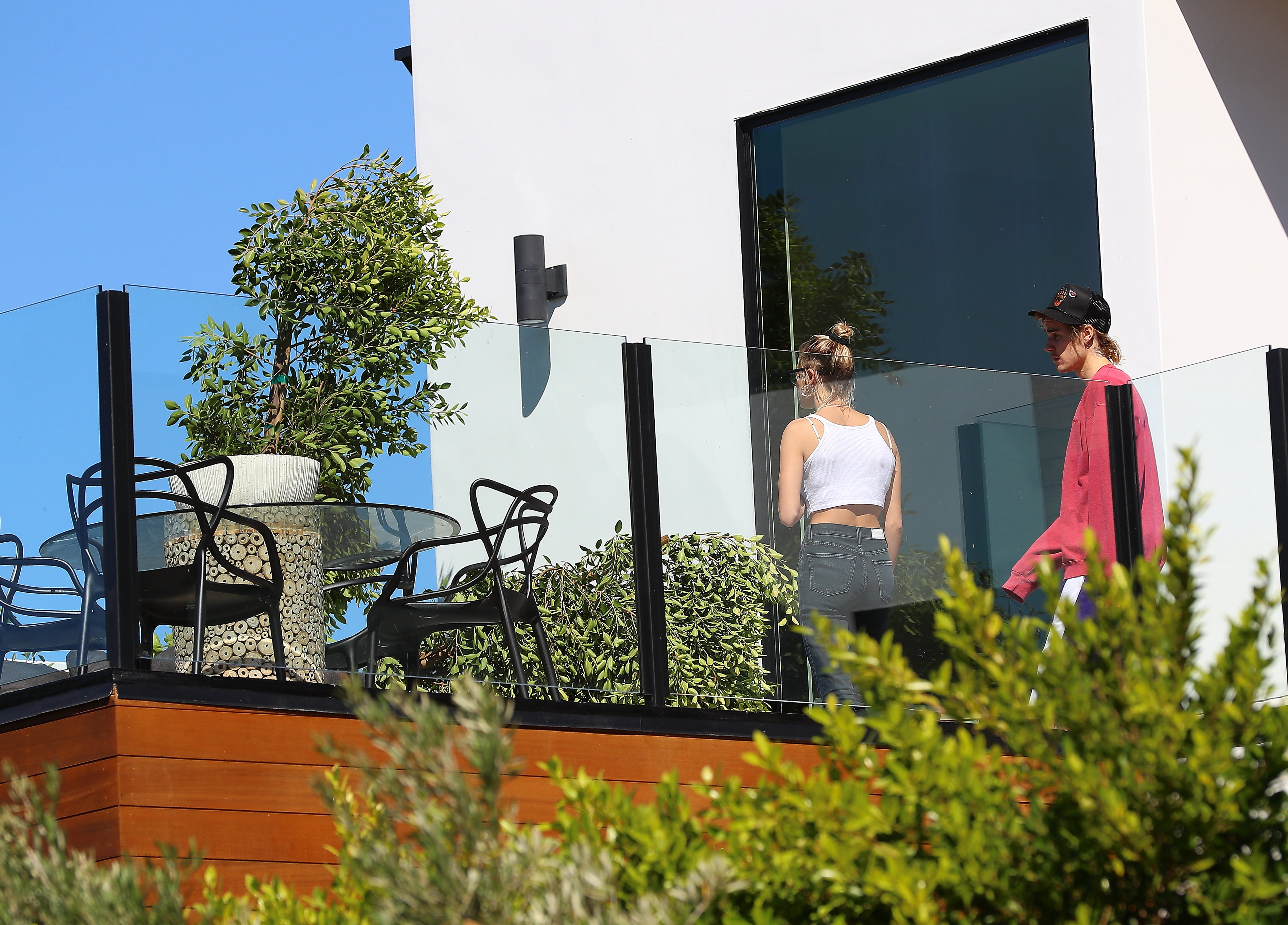 Justin Bieber and Hailey on the ledge of a home they are viewing to buy in Los Angeles, CA