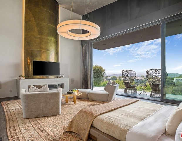 32188892 8648387 The Master Bedroom Features A Brass And Concrete Fireplace With A 2 1597956565473