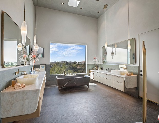 32188900 8648387 The Tub Sits In Front Of A Huge Window With Sweeping Views Of Th A 4 1597956565540